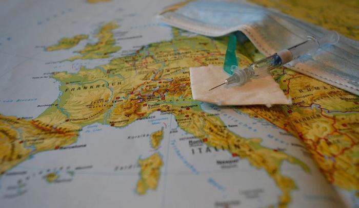 шприц с вакциной на фоне карты